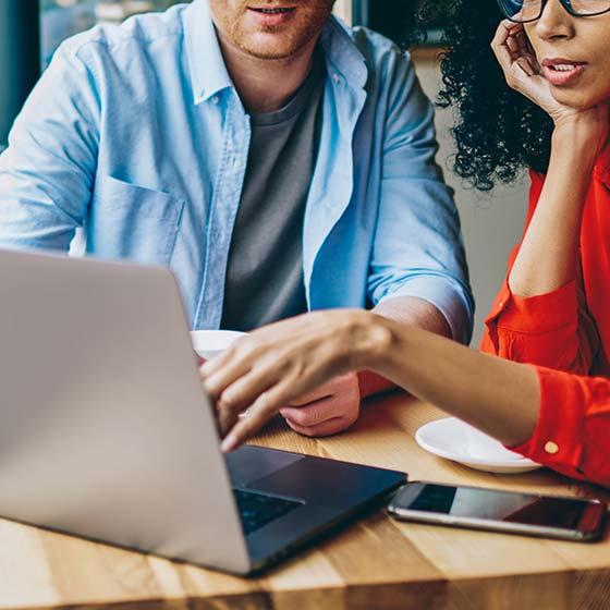 Um homem de camiseta azul e uma mulher de camiseta vermelha, sentados numa mesa observando um notebook