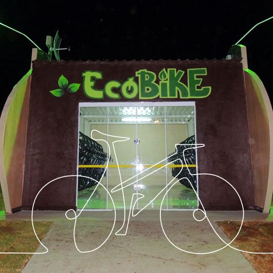 Uma construção de cor cinza e alguns grafites, possui porta de vidro e o nome EcoBike na cor verde. Por cima da imagem, o desenho de uma bicicleta.