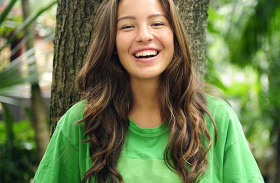 Uma mulher de cabelos castanhos e encaracolados, sorri e usa uma camiseta verde.