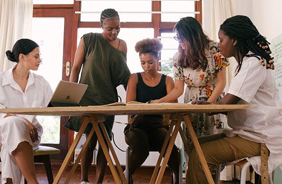 Pessoas reunidas em volta de uma mesa analisando gráficos